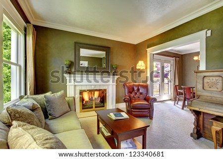 Elegant classic green living room with fireplace and piano. - stock photo
