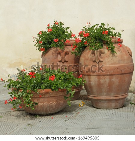 elegant classic  tuscan terracotta plant containers   with geranium flowers on italian terrace, Europe - stock photo