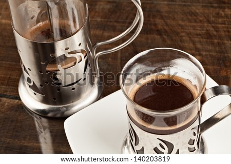 Elegant coffee cup served along with filter against heavy polished wooden table - stock photo