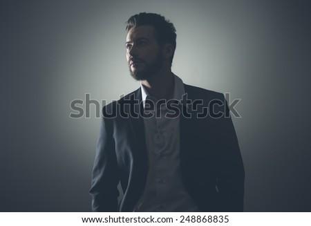 Elegant confident businessman posing on dark background - stock photo
