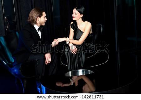 Elegant couple admiring each other, dark background. - stock photo