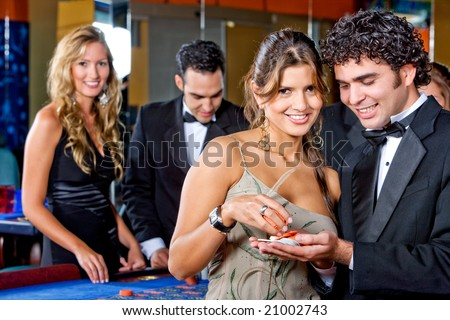 elegant couple at the casino smiling and betting on the roulette