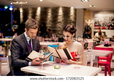 elegant couple choosing meal from menu at restaurant - stock photo
