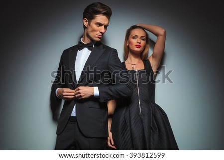 elegant couple in black posing in gray studio background. man stands in front fixing his jacket looking away while woman fixing her hair is looking at the camera.  - stock photo