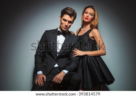 elegant couple in black posing in studio background looking at the camera. man is seated while woman stands by his side with hands on his shoulder and arm - stock photo