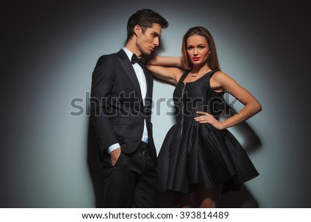 elegant couple in black posing. the man is standing with hands in pockets looking at the woman while the woman with one hand on waist and one hand on his shoulder is looking at the camera.  - stock photo