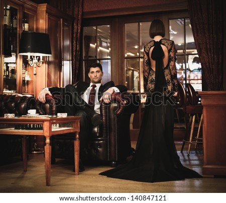 Elegant couple in formal dress in luxury cabinet - stock photo