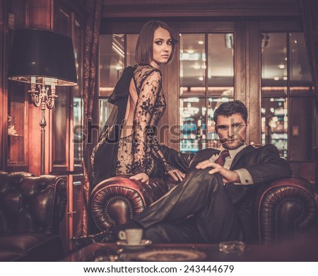 Elegant couple in formal dress in luxury cabinet interior - stock photo