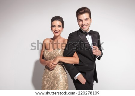 Elegant couple laughing for the camera while holding arm to arm. On grey background. - stock photo