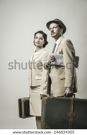Elegant couple leaving for vacations with luggage, 1950s style - stock photo