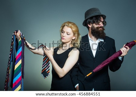 Elegant couple of young blond woman in black dress and handsome bearded hipster man in hat with umbrella choose neckties on grey wall