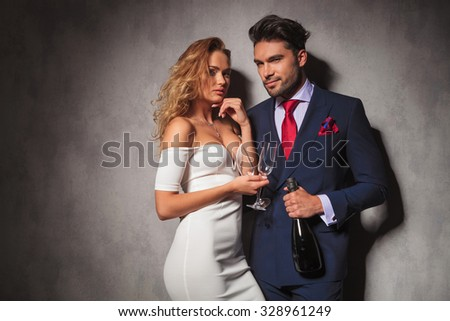 elegant couple ready to party with a bottle of champagne in studio - stock photo