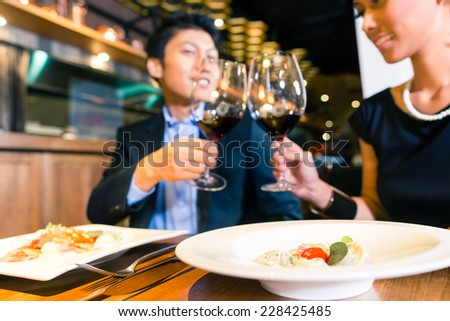 Elegant couple toasting with red wine