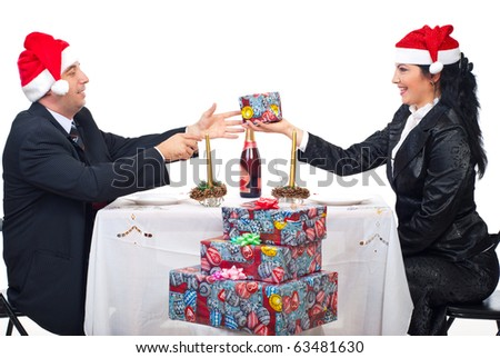 Elegant couple with Santa hats sharing Christmas gift and sitting together at table