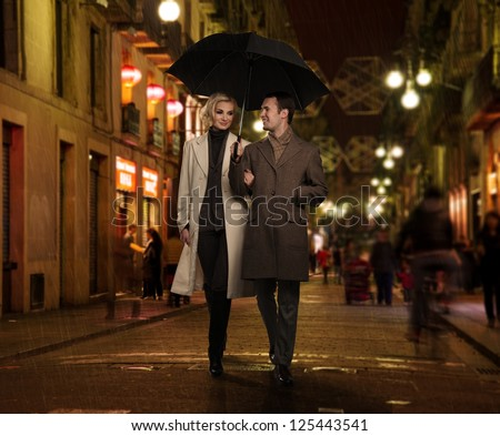 Elegant couple with umbrella outdoors on rainy evening - stock photo
