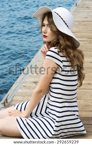 elegant cute woman , in white and summer dress with hat , sitting on bridge during a sunny day on the sea . - stock photo