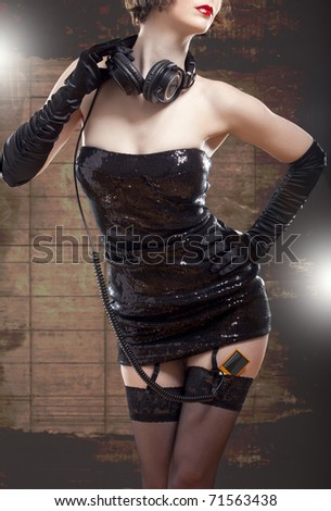 Elegant disco girl listening to music in shiny clothes - stock photo