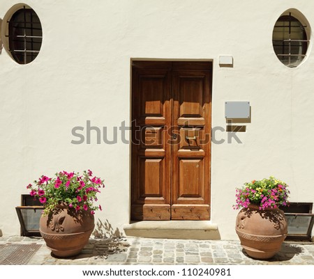 elegant doorway to the  house with terracotta containers for blooming plants,  Emilia - Romagna,Italy, Europe - stock photo