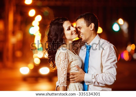 Elegant dressed man is tenderly embracing happy laughing woman at bright night street lights background.