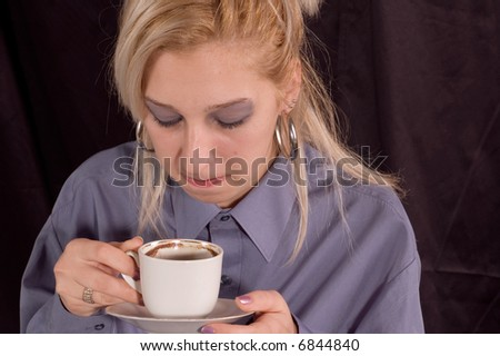 Elegant dressed young pretty woman drinking coffee