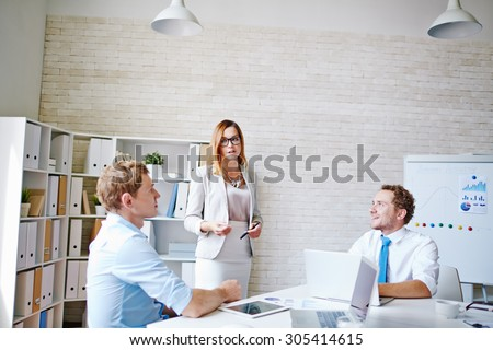 Elegant employee explaining financial data to colleagues