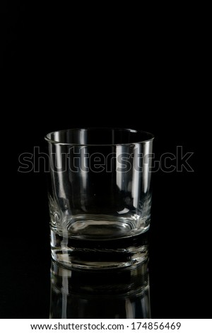 Elegant empty transparent stemmed glass silhouetted by light reflections on a black background - stock photo