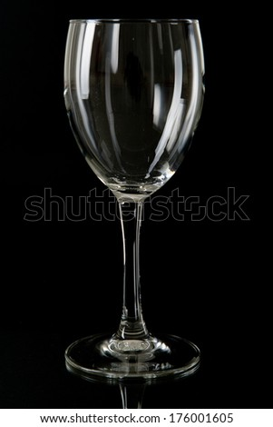 Elegant empty transparent stemmed glass silhouetted by light reflections on a black background