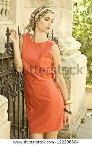 Elegant fashion brunette in red dress posing with cap outdoor by the fence