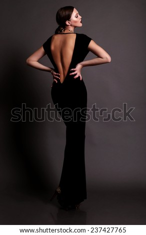Elegant fashion photo of glamor beautiful brown-haired woman in a black sexy dress with open back wearing gold jewelry and posing in the studio,luxury - stock photo