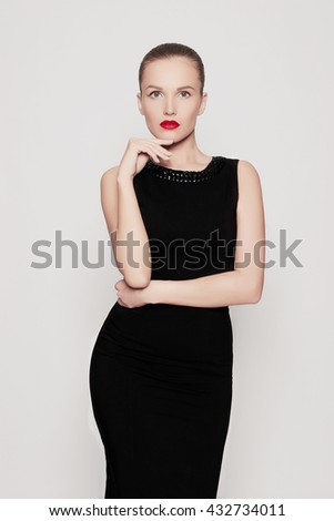 Elegant fashion photo of glamor beautiful young woman in a black sexy dress.beauty brunette girl with red lips - stock photo