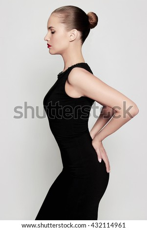 Elegant fashion photo of glamor beautiful young woman in a black sexy dress posing in the studio,luxury.beauty brunette girl with red lips - stock photo