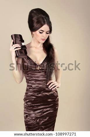 Elegant Fashion Sexy Woman in chocolate dress with small bag - stock photo