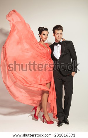 Elegant fashion woman fluttering her coral dress while embracing her lover, both looking away from the camera. - stock photo