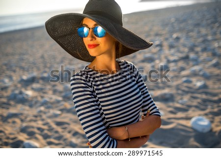 Elegant fashion woman in stripped dress with a hat and sunglasses standing on the beach on sunset - stock photo