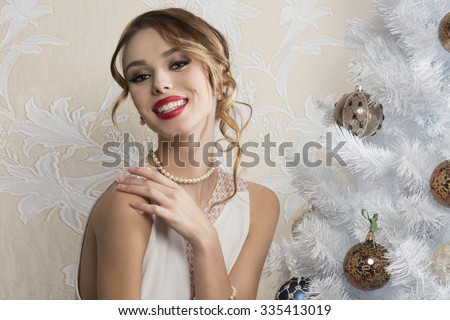 elegant fashion woman with happy expression, hair-style and cute make-up posing near decorated christmas tree