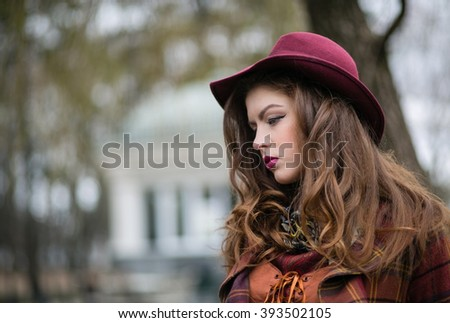 Elegant Fashionable beautiful young woman in a vintage hat burgundy color and the old coat walks on cold autumn park, fashion, style, closeup portraite