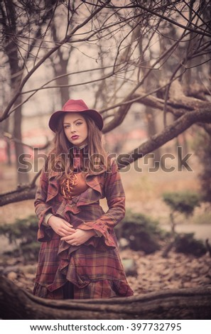 Elegant Fashionable beautiful young woman in a vintage hat burgundy color and the old  English coat walks on cold autumn park, fashion, english style
