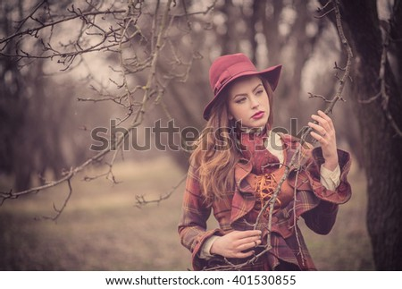 Elegant Fashionable beautiful young woman in a vintage hat burgundy color and the old  English coat walks on cold autumn park, fashion, style   - stock photo