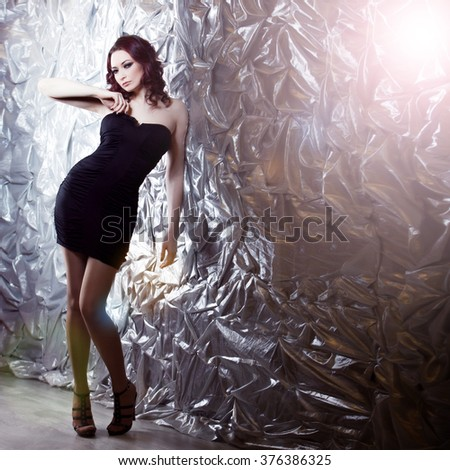 elegant fashionable woman  in  black dress on  silver background