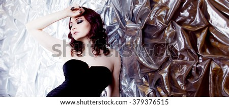 elegant fashionable woman  in  black dress on  silver background - stock photo