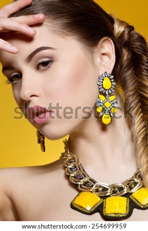 Elegant fashionable woman on yellow background. Fashion Portrait Of Beautiful Luxury Woman With Jewelry - stock photo
