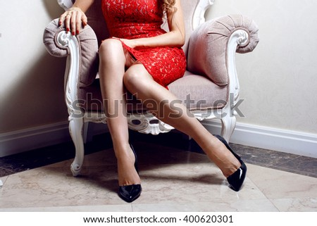 Elegant fashionable woman wearing black high heels and red dress , sit on beautiful chair - stock photo