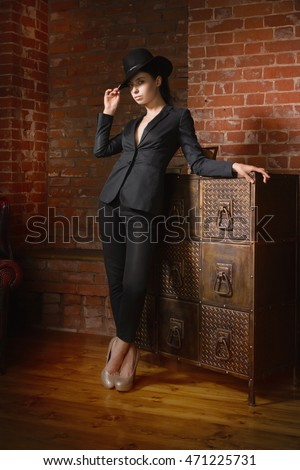 Elegant fashionable woman wearing black suit and hat in a vintage interior. Noir film style