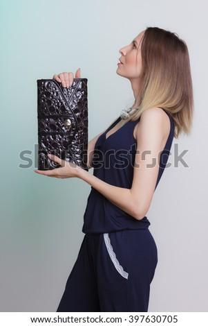 Elegant fashionable woman with leather handbag. Stylish girl on green holding black bag. Female fashion vogue. Studio. Side profile view. - stock photo