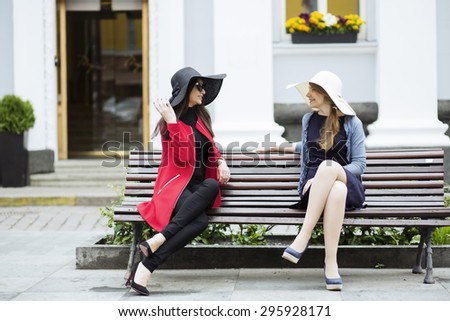 Elegant female couple chatting in the square - stock photo