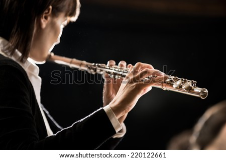 Elegant female flutist playing flute on dark background.
