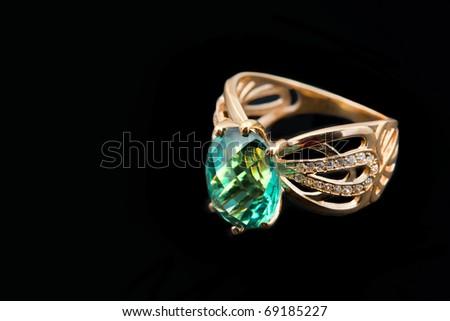 Elegant female golden jewelry ring with   emerald - stock photo