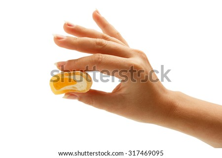 Elegant female hand holding delicious japanese mochi rice cake with a fruit filling isolated on white background. Closeup.