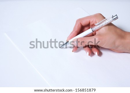 Elegant female hand with French manicure writes beautiful pen on a blank sheet - stock photo