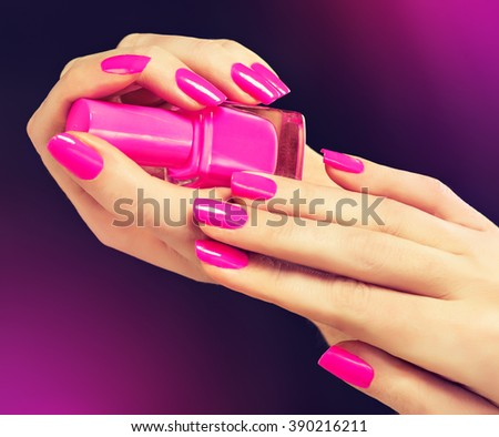 Elegant female hands with pink manicure on the nails . Beautiful fingers holding the nail Polish . - stock photo